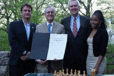 "L to R: Marc Rotenberg, David Mehler (holding the ""Chess in the Schools Day"" resolution) Councilmember Tommy Wells, Rochelle Balantyne."