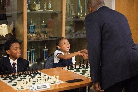 GM Maurice Ashley greets a student before a simultaneous exhibition at the U.S. Chess Center